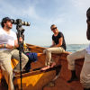 Three people on a small boat off with video camera, of the coast of the Gambia